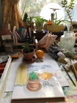 Still life with orange and potted plant on drawing table